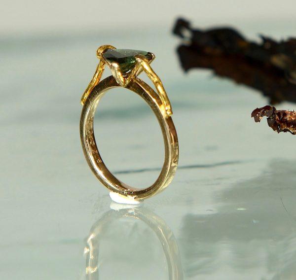 Ring i 14kt 585 guld med 24kt guld grene der holder en grøn turmalin